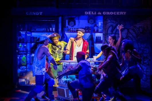 Sam Mackay as Usnavi and the cast of In The Heights. Photo Credit Johan Persson